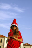 Beautiful girl dressed as Santa Claus with glasses — Stock Photo