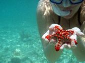 Submerged woman with starfish in his hand — Stock Photo