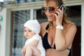 Mom talking on the phone with baby in her arms — Stock Photo