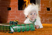 Cute little santa baby with New years gifts on the fireplaces background — Foto Stock