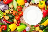 Légumes biologiques frais autour de la plaque blanche — Photo