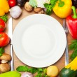 Organic Vegetables Around White Plate with Knife and Fork — Stock Photo #22623735