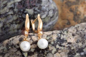 Gold Earrings with Diamonds and Pearls on the natural stones bac — Foto Stock