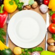 Organic Vegetables Around White Plate with Knife and Fork — Stock Photo #35269991