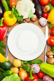 Organic Vegetables Around White Plate with Knife and Fork — Stock Photo