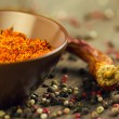 Saffron in brown bowl with chili and pepper — Stock Photo #48791763