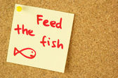 Feed the fish remind sticker on cork — Stock Photo