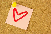 Pink sticker with draw heart on the corkboard — Stock Photo