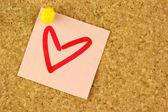 розовый стикер с обратить сердца на пробковой доске — Стоковое фото