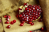 Raw pomegranate with seeds on sacking — Stock Photo