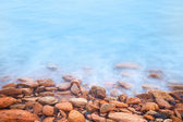 Shore of the sea, stones  and flowing water  — Stock Photo