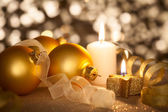 Golden Christmas background with candles, baubles and ribbons  — Photo