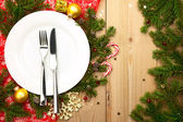 Christmas Dinner - white plate with cutlery on wooden background — Stock Photo