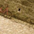 Stock Photo: Old child bicycle with cobble and wall