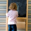 Cute young caucasian boy writing on a blackboard — Stok fotoğraf #14910299