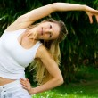 Stock Photo: Blonde girl in park doing yoga