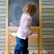 Cute young caucasian boy writing on a blackboard — Foto Stock