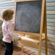 Cute young caucasian boy writing on a blackboard — Foto de Stock