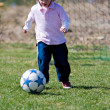 Cute young caucasian boy playing football or soccer — Stock Photo