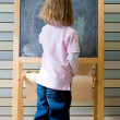 Cute young caucasian boy writing on a blackboard — Stok fotoğraf