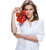 Young beautiful woman with bunch of tomatoes in hand isolated on white background — Zdjęcie stockowe