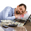 Worried businessman sleeping at office desk being overloaded with work and accounting money — Stock Photo