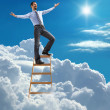 Successful businessman with open arms standing at the top of ladder high in the sky — Stock Photo