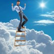 Young modern businessman excited with his success standing at the top of ladder high in the sky — Stock Photo