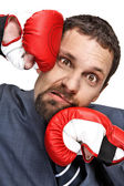 Close-up young businessman struck in the face by hands in boxing gloves isolated on white background — Stock Photo