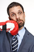 Close-up young business man struck by hand in boxing glove isolated on white background — Stock Photo