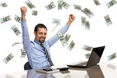 Businessman with his hands raised while working on laptop with money rain — Stock Photo