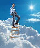 Young confident businessman standing at the top of ladder high in the sky and showing down by the hand with forefinger — Stock Photo