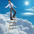 Young confident businessman standing at the top of ladder high in the sky lends a helping hand — Stock Photo #28996603
