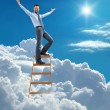 Young confident businessman standing at the ladder high in the sky spread his arms — Stock Photo