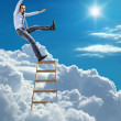 Stock Photo: Young confident businessmstanding at ladder high in sky falls from top