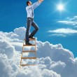 Stock Photo: Young confident businessmstanding at ladder high in sky pulls hands to sky