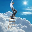 Постер, плакат: Young confident businessman standing at the ladder high in the sky reaches the top