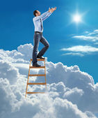 Young confident businessman standing at the ladder high in the sky pulls hands to the sky — Stock Photo