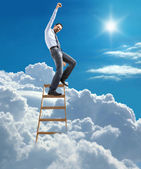 Young confident businessman standing at the ladder high in the sky reaches the top — Stock Photo