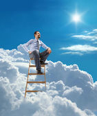 Young confident businessman sits atop at the ladder high in the sky — Stock Photo