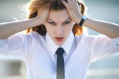 Distressed young woman holds her head with both hands — Stock Photo