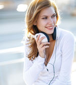 Enchanting young woman holds the headphones — Stock Photo