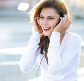 Pleasant young woman puts her headphones on — Stock Photo