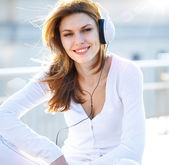 Captivating young woman listens to music through headphones — Stock Photo