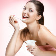 Charming woman eating yogurt — Stock Photo #32966957