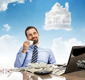 Daydreaming businessman with a cup of tea with head in the clouds — Stock Photo