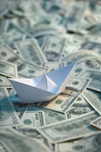 Origami paper ship at sea of money — Stock Photo
