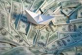 Paper boat at sea of money — Foto Stock