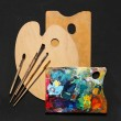 Paint brushes and wooden palette used for painting — Stockfoto