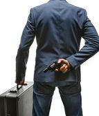 Hiding gun behind his back — Stock Photo